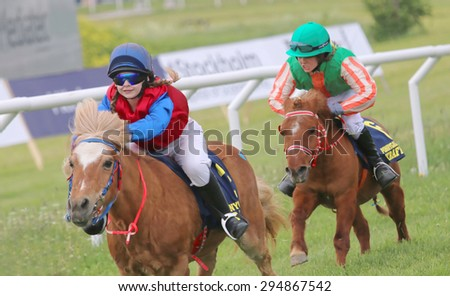 STOCKHOLM - JUNE 06: Tough race between two pony race horses at the Nationaldags Galoppen at Gardet. June 6, 2015 in Stockholm