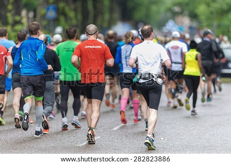 STOCKHOLM - MAY 30: Back of a group of people at the streets of Stockholm at ASICS Stockholm Marathon 2015. May 30, 2015 in Stockholm, Sweden. Runners from 101 nations were registered in 2015 - stock photo