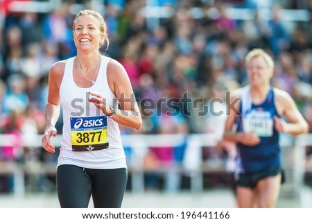 STOCKHOLM - MAY 31: Blonde woman running the final stretch at Stockholm Stadion in ASICS Stockholm Marathon 2014. May 31, 2014 in Stockholm, Sweden. - stock photo