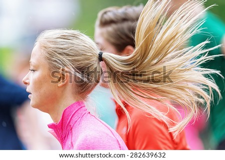 STOCKHOLM - MAY 30: Closeup of a longhaired woman in ASICS Stockholm Marathon 2015. May 30, 2015 in Stockholm, Sweden. Runners from 101 nations were registered in 2015 - stock photo