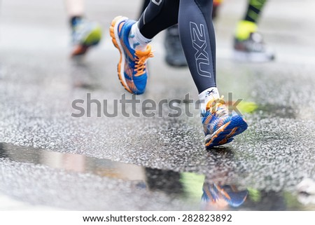 STOCKHOLM - MAY 30: Colorful running shoes with reflections in the wet asphalt at ASICS Stockholm Marathon 2015. May 30, 2015 in Stockholm, Sweden. Runners from 101 nations were registered in 2015 - stock photo