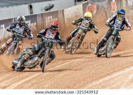 STOCKHOLM - SEPT 26, 2015: Action image of a group of speedway racers going into a curve at the TEGERA Stockholm FIM Speedway Grand Prix at Friends Arena in Stockholm. - stock photo