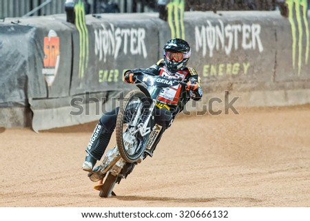 STOCKHOLM - SEPT 25, 2015: Andreas Jonsson from Sweden doing a wheelie in a curve at the TEGERA Stockholm FIM Speedway Grand Prix at Friends Arena in Stockholm. - stock photo