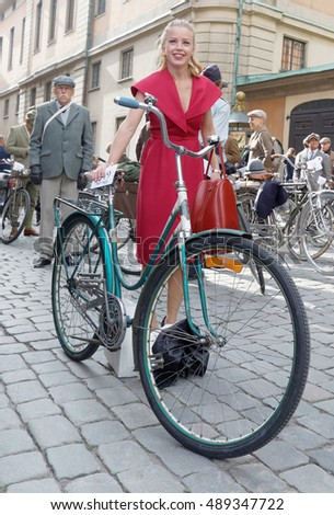 STOCKHOLM - SEPT 24, 2016: Bicycle and young woman dressed in old fashioned red dress in the Bike in Tweed event September 24, 2016 in Stockholm, Sweden