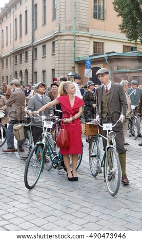 STOCKHOLM - SEPT 24, 2016: Smiling woman dressed in a red dress leading bicycles in the Bike in Tweed event September 24, 2016 in Stockholm, Sweden