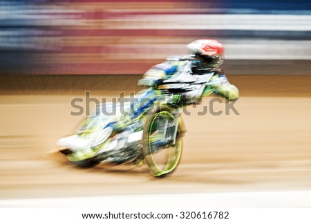STOCKHOLM - SEPT 25, 2015: Speedway rider in motionblur at the TEGERA Stockholm FIM Speedway Grand Prix at Friends Arena in Stockholm. - stock photo
