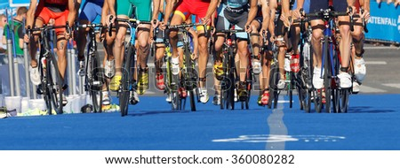 STOCKHOLM, SWEDEN - AUG 23, 2015: Triathlete cycle wheels, legs and shoes in the Men's ITU World Triathlon series event August 23, 2015 in Stockholm, Sweden - stock photo