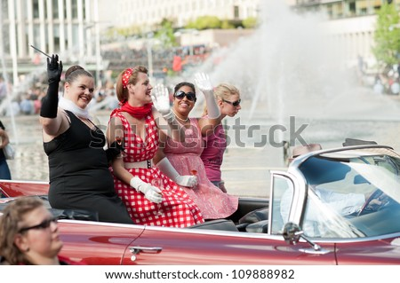 STOCKHOLM, SWEDEN - AUGUST 4: Four ladies ride a cabriolet at Stockholm Pride Parade on August 4, 2012 in Stockholm which attracts an estimated 50000 participants and 500000 spectators. - stock photo