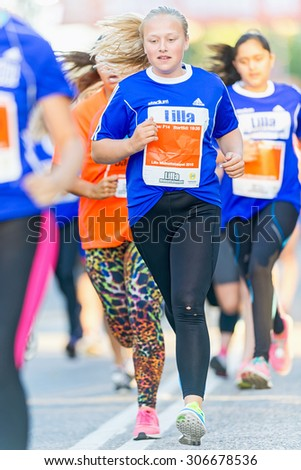 STOCKHOLM, SWEDEN - AUGUST 15, 2015: Girl running just after the start at Lilla Midnattsloppet for aged 14. The track is 1775 meters and the runners are aged 8-15 years. - stock photo