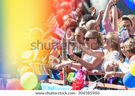 STOCKHOLM, SWEDEN - AUGUST 1, 2015: Happy participants waving to the crowd at the Pride parade in Stockholm. Approx 400.000 spectators at the streets. - stock photo