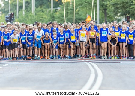 STOCKHOLM, SWEDEN - AUGUST 15, 2015: Starting field with nervous runners just before the start Lilla Midnattsloppet for runners aged 13. The track is 1775 meters and the runners are aged 8-15 years. - stock photo