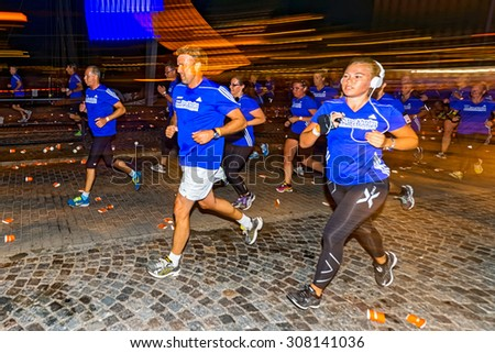 STOCKHOLM, SWEDEN - AUGUST 15, 2015: Woman runner with headphones motion blur on the streets of Soder at Midnattsloppet or the Midnight run. The track is 10 km and goes thru the streets of Stockholm. - stock photo