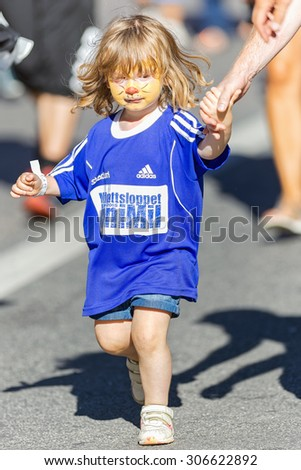 STOCKHOLM, SWEDEN - AUGUST 15, 2015: Young girl holding dads hand at the Minimil for the youngest runners at Midnattsloppet. The track is 300 meters and the runners are aged 2-8 years. - stock photo