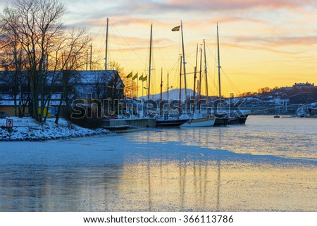 STOCKHOLM, SWEDEN - JAN 16, 2016: View over docked boats at Djurgarden with Junibacken. Reflections in the winter ice during morning. - stock photo