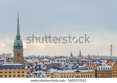 STOCKHOLM, SWEDEN - JAN 8, 2015: View over Stockholm Old Town with snowy roofs. Tyska kyrkan - stock photo