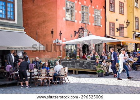 STOCKHOLM, SWEDEN-July 9, 2015: Busy sidewalk cafes in picturesque historic Gamla Stan, the oldest neighborhood in Stockholm. The area is a popular destination for visitors of all ages. - stock photo