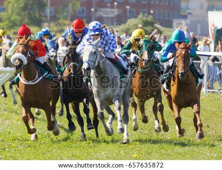 STOCKHOLM, SWEDEN - JUNE 06, 2017: Jockeys on gallop arabian race horses storming ahead at Nationaldags Galoppen at Gardet. June 6, 2017 in Stockholm, Sweden