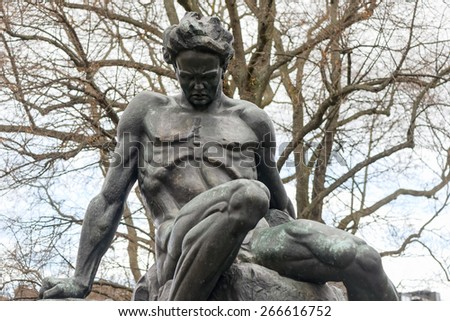 STOCKHOLM, SWEDEN - MAR 31: Statue of August Strindberg at Tegnerlunden in light snowfall, March 31, 2015 in Stockholm, Sweden. Massive statue of August Strindberg by Carl Eldh, from 1942. - stock photo