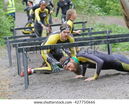 STOCKHOLM, SWEDEN - MAY 14, 2016: Group of struggling people crawling under bars in the obstacle race Tough Viking Event in Sweden, April 14, 2016