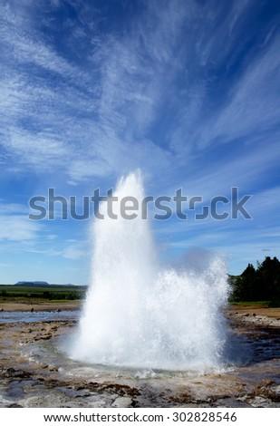 Stokkur geyser eruption, Iceland. Blue sky in a sunny day portrait orientation - stock photo