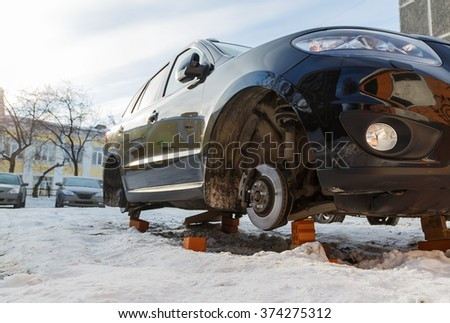 stolen car without wheels winter morning on the Russian car park bottom view - stock photo
