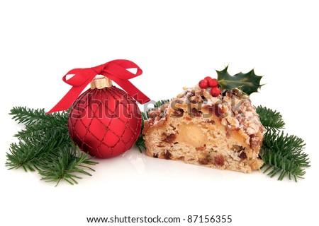 Stollen christmas cake with holly berry, red bauble decoration and blue pine fir sprigs isolated over white background.