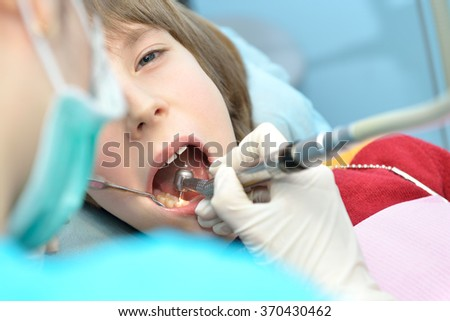 Stomatologist. Dental health. Female dentist curing a child patient in doctor's consulting room. Pediatric dentist. - stock photo