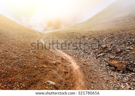 stone and ground brown Mountain road in valley without plants - stock photo