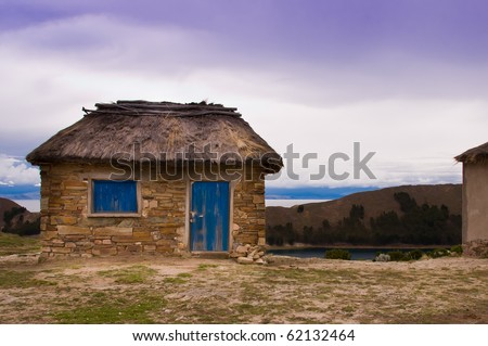 Stone and thatch hut which is located on an island, Isla del Sol, on the Bolivian side of Lake Titicaca. - stock photo