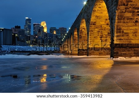 Stone Arch Bridge and Minneapolis Skyline at Night - stock photo