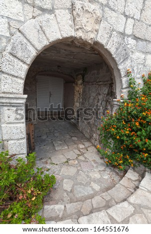 Stone arch, entrance to ancient house in Perast town, Montenegro