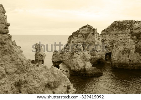 Stone arches, caves, rock formations at Dona Ana Beach (Lagos, Algarve coast, Portugal) in the evening light. Aged photo. Sepia. - stock photo