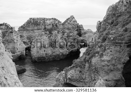 Stone arches, caves, rock formations at Dona Ana Beach (Lagos, Algarve coast, Portugal) in the evening light. Aged photo. Black and white. - stock photo