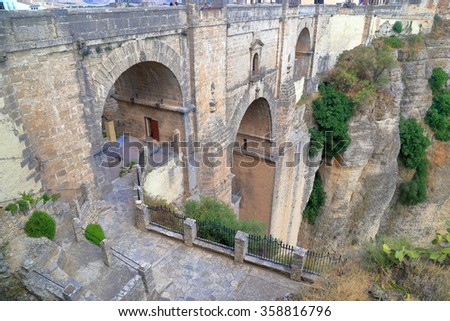 Stone arches of the New Bridge span across a deep gorge in Ronda, Andalusia, Spain