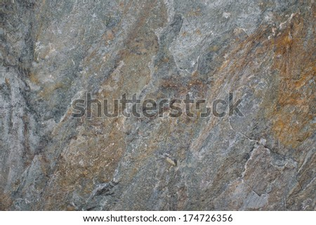 Stone background texture of a piece of slate with a rough surface used in construction for paving, flooring and as a wall covering - stock photo