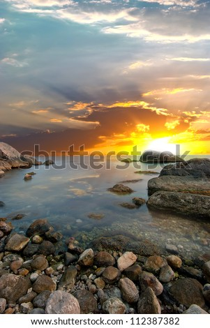 Stone beach and the sun setting behind the stone. natural landscape - stock photo