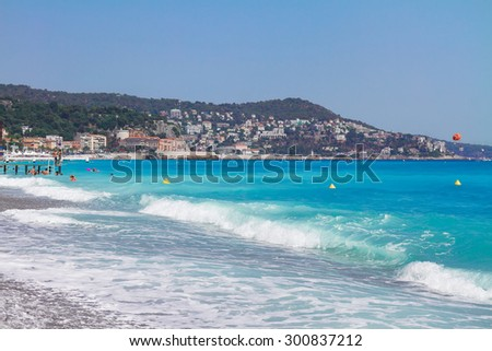 stone beach and turquiose water of cote dAzur at Nice, France - stock photo