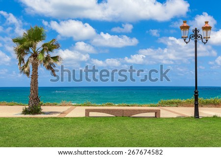Stone bench between palm and decorative lamppost with beautiful view on Mediterranean sea under blue sky with white clouds in Israel. - stock photo