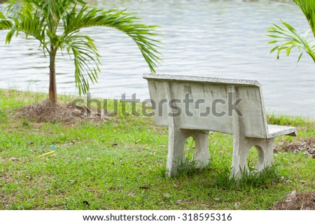 Stone bench in the grass. Adjacent to the pool in the park. - stock photo