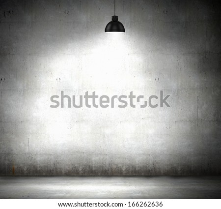 Stone blank wall illuminated with hanging above lamp. Place for text - stock photo