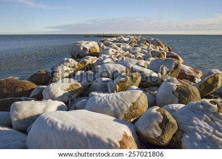 Stone breakwater with last snow. - stock photo