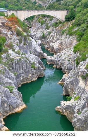 Stone bridge across limestone gorge and river in Saint Guilhem le Desert, Languedoc Roussillon, France - stock photo