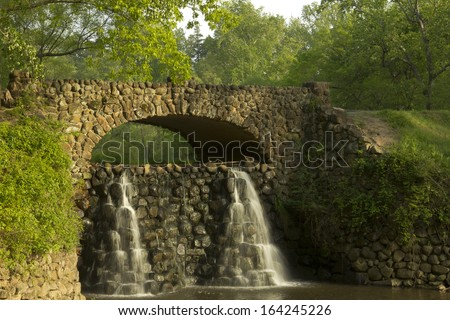 Stone Bridge and Waterfall in Reynolda Gardens in Winston-Salem NC - stock photo