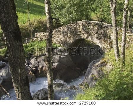 stone bridge over stream - stock photo