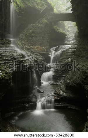 stone bridge with two waterfalls in gorge with misty rain - stock photo