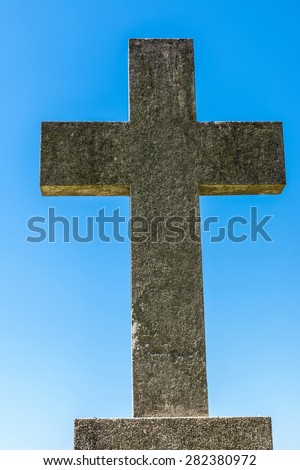Stone cross against blue sky in a cemetery. - stock photo