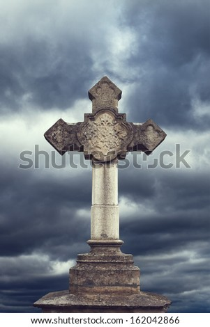 stone cross on dark sky - stock photo