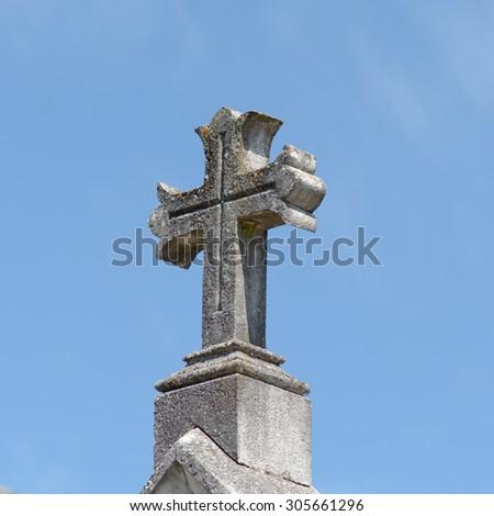Stone cross on grave in cemetery - stock photo