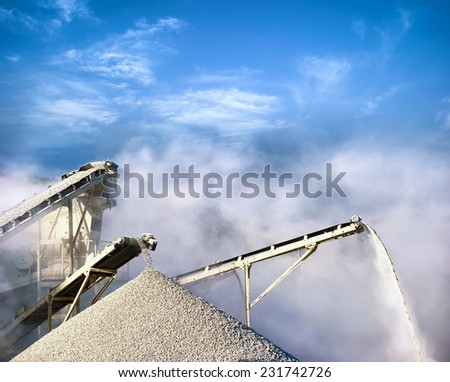 Stone crushing equipment, working conveyor loading gravel and producing air pollution with dust and smog  - stock photo