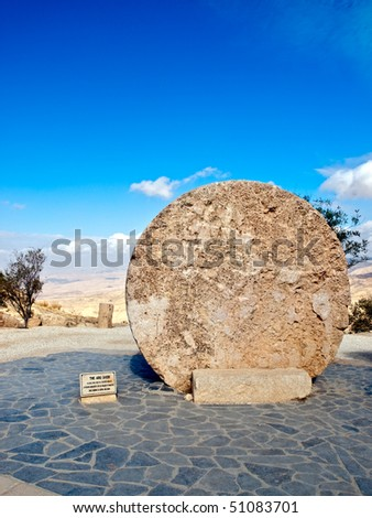 Stone door of the Moses grave with a Jordanian desert valley in the back Bethany, Jordan. Copy space on the left. - stock photo